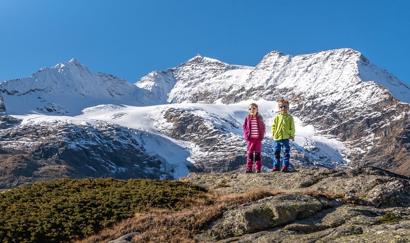 kids standing in front of mountain