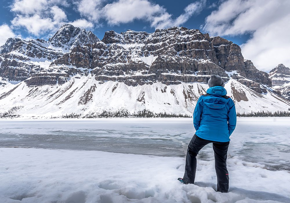 person staying at the frozen Bow lake in the Icefields Parkway in Canada