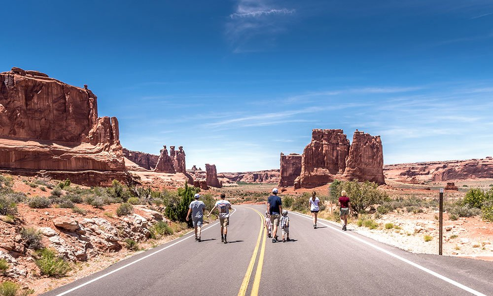 friends walking down the road in Arches Nation Park Utah