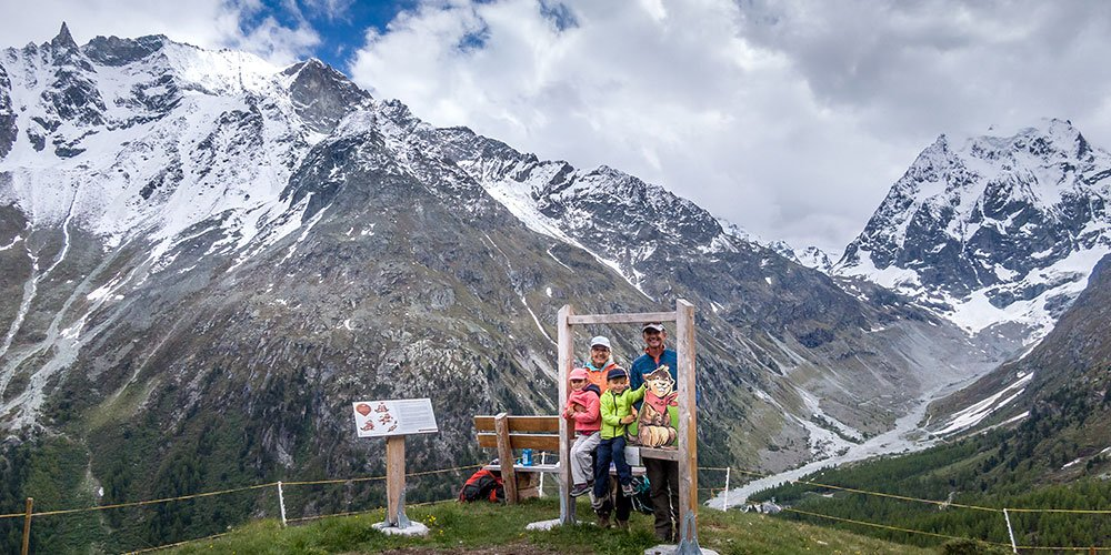 family standing at a photo frame in Arolla on the Marmot trail