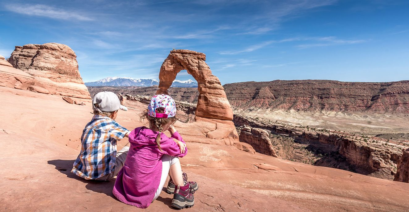 kids sitting in front of the delicate arch in arches national park