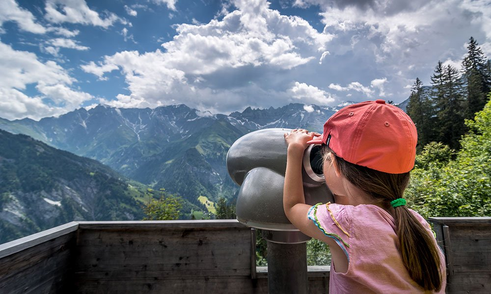 girl looking though binoculars at the Riesenwald in Elm