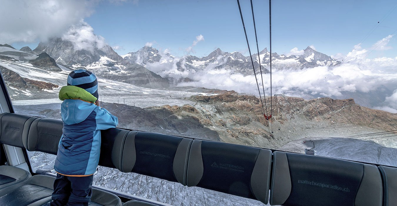 little boy marvelling at the Matterhorn from the inside of the glacier paradise cabine in Zermatt