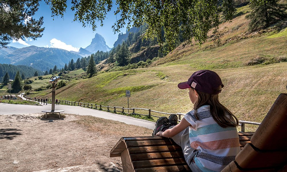 girl sitting on a bench looking at the Matterhorn