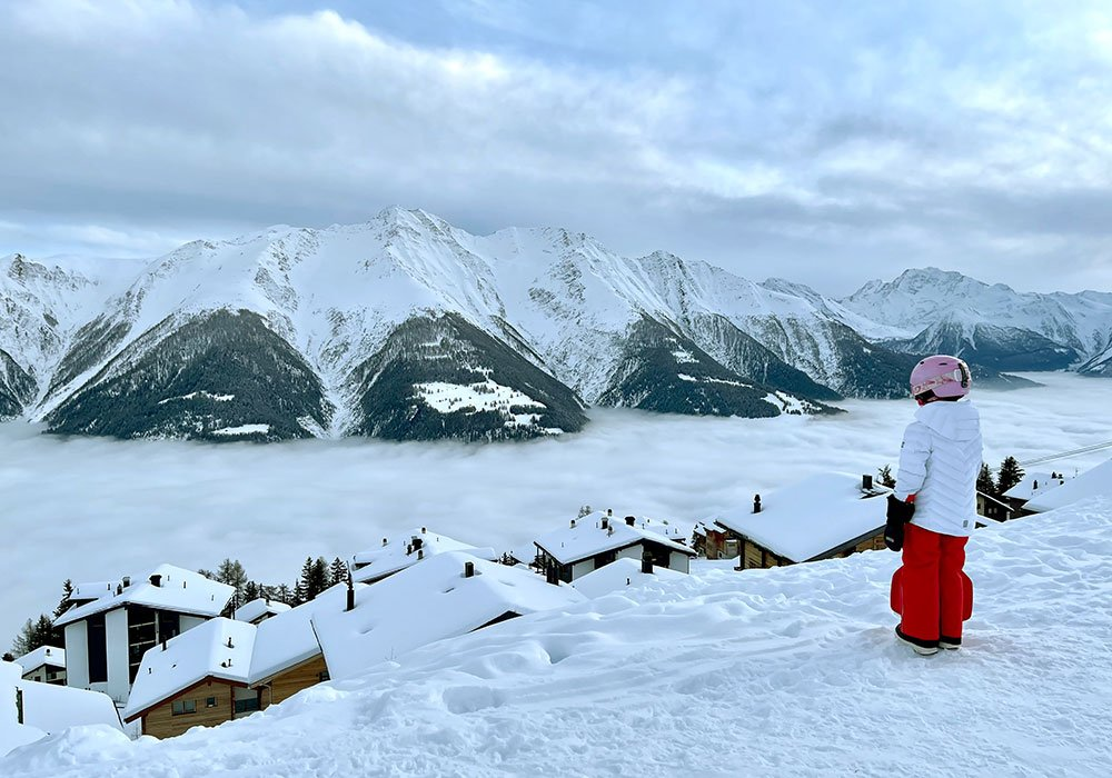 girl standing above the clouds in Bettmeralp