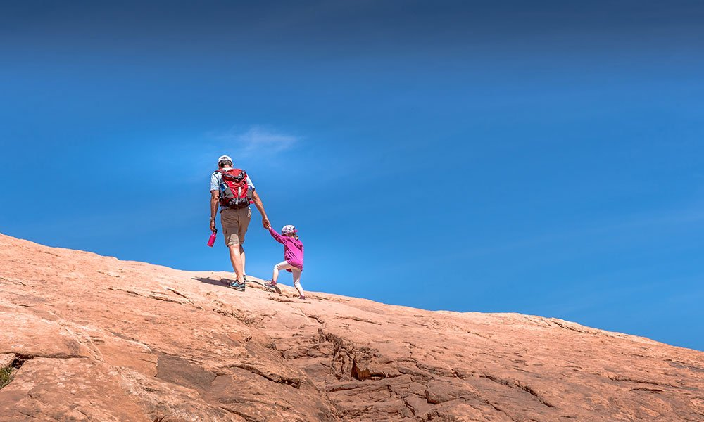 father and daughter hiking to Delicate Arch in Moab