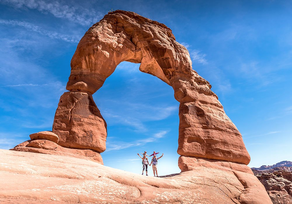 family standing under Delicate Arch, after hiking delicate arch