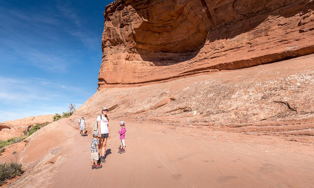 people standing on narrow path whilst hiking delicate arch with kids