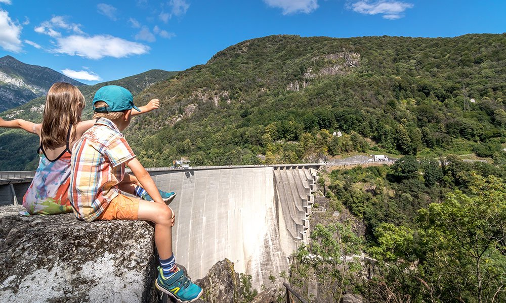 children sitting at the High Dam in Verzasca Ticino Switzerland