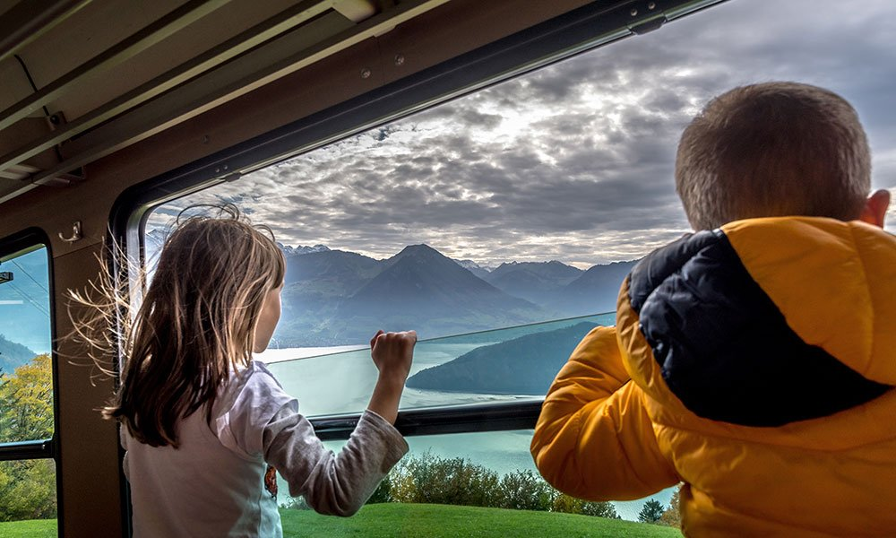 children looking out of the Rigi Kulm train on the way to one of the most beautiful views in Switzerland the Rigi
