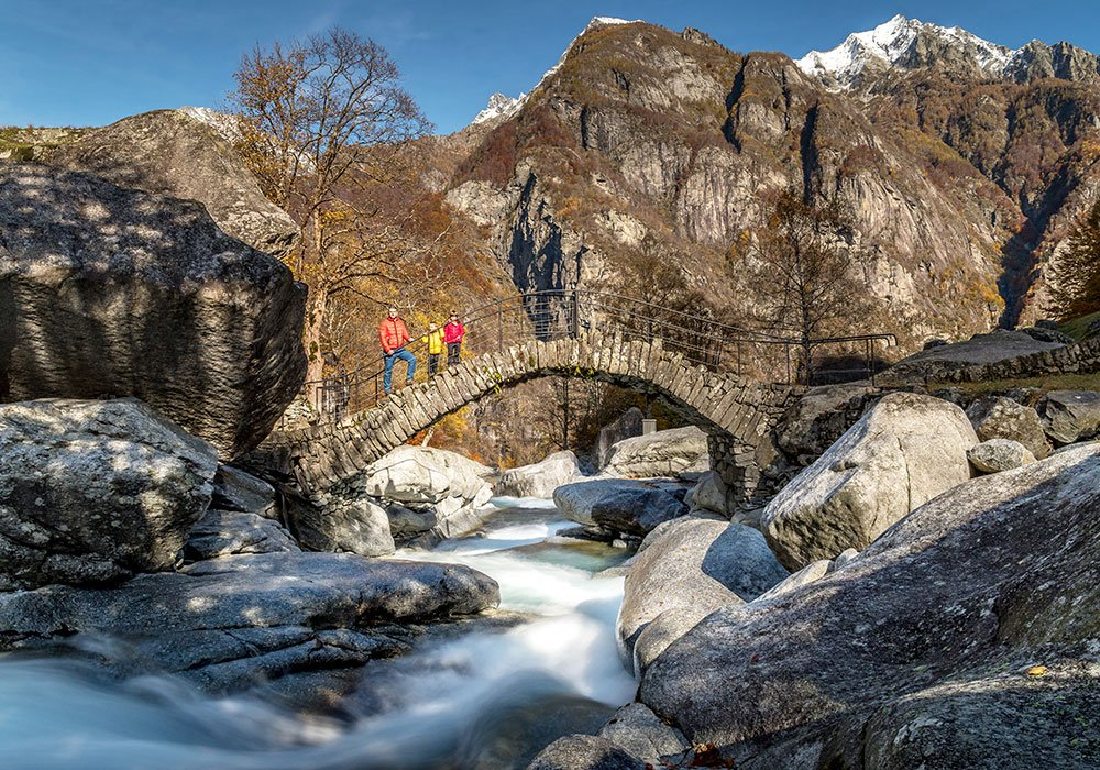 family standing on the Puntid bridge in Val Calnégia in Foroglio Ticino Switzerland
