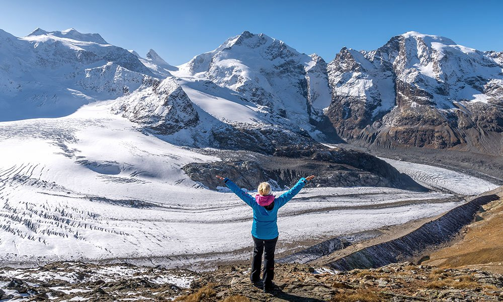 woman standing in from of Piz bernina at Diavolezza in engadin . best views in Switzerland
