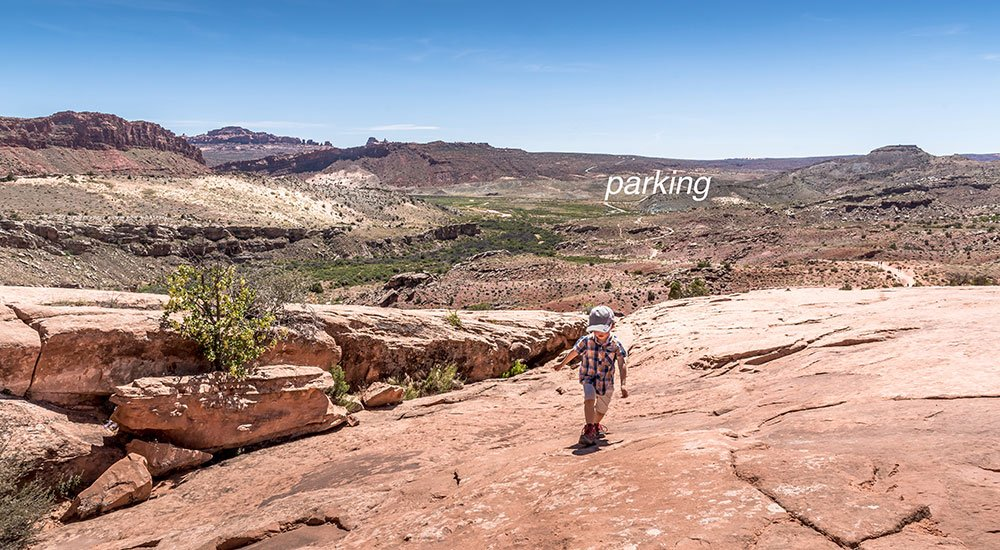 boy hiking delicate Arch during the sunshine