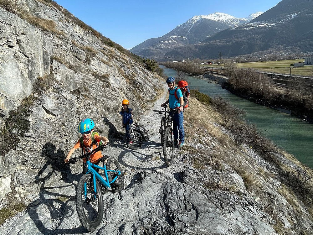 father with kids on a cycling route in Switzerland