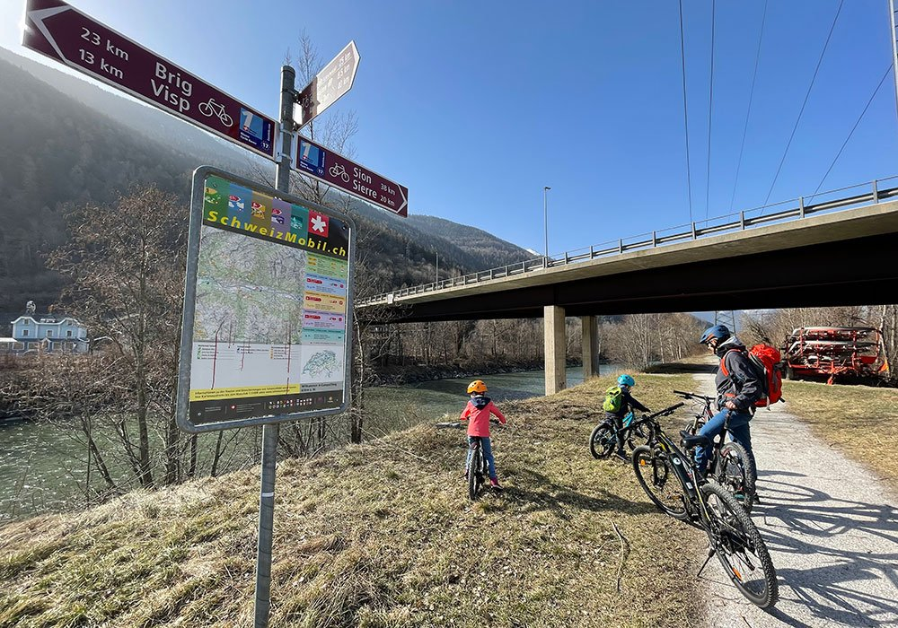 Family standing by a Official Cycling Route signes from Switzerland