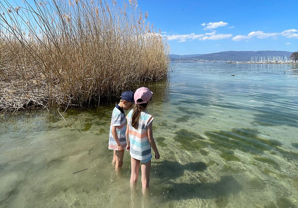 kids in the water at lake Neuchatel in the 3 lake region